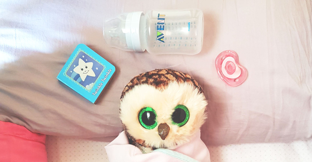 Owl surrounded by a book, a milk bottle and a pacifier