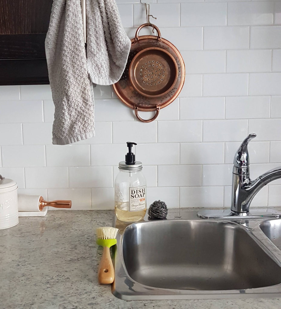 A picture of a section of a kitchen. There is a sugar can and rolling pin sitting on the counter top beside the sink. Right above the sink is a hanging grey towel and a copper strainer. On the sink is a dish soap with a stainless steel scrubber beside it with a dish brush in front.