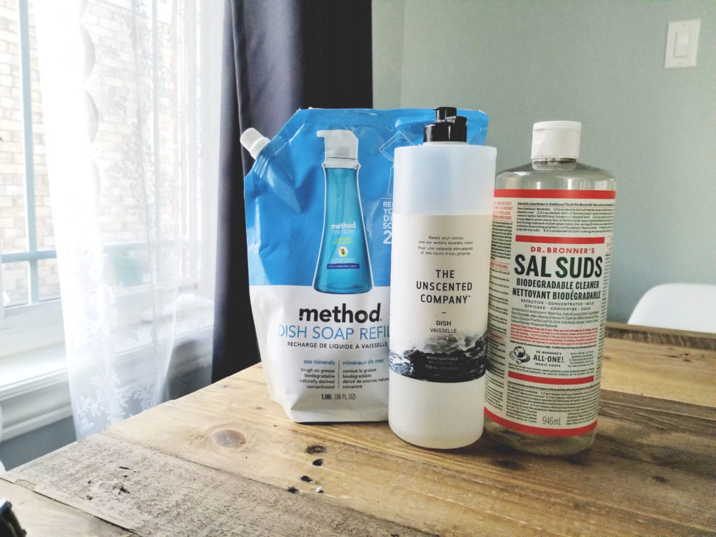 A picture of three different kinds of dish soaps sitting on a table. The three soaps presented here are: Method Dish Soap Refill; The Unscented Company and Dr. Bronner's Sal Suds Biodegradable Cleaner.