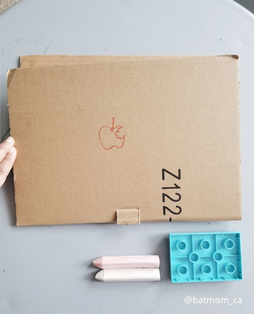 The cardboard laptop is placed on the circle blue-grey table top. Along with the laptop is a duplo block and a couple of chalks.